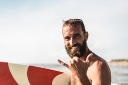 Surfer happy with surf surfing smiling doing hawaiian shaka hand sign for fun during surf session in ocean waves on beach vacation -  Surfing travel destination - Friendly greeting in surfer culture