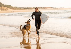 Surfer having fun with best friend german shepherd running and playing on dog-friendly beach at sunset. Summer fun surfing vacation with your dog, pet friendly trip and outdoors adventure lifestyle.