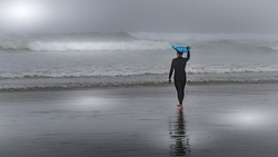 Surfer heading into the Waves in the Dense Fog to surf in Cox Bay at the Pacific Rim National Park on Vancouver Island, British Columbia, Canada