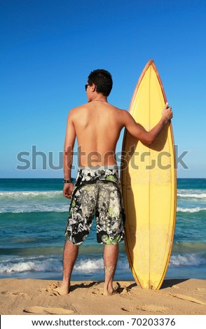 Stock Photo Surfer holding a surf board on beach