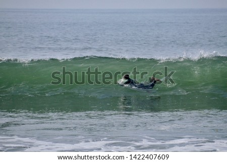 Surfer in wetsuit diving through a translucent blue green wave in Newport Beach, California #1422407609