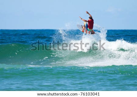 surfer jumps over the big wave with a splash