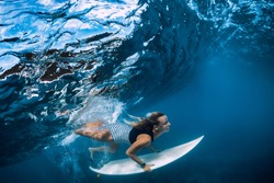 Surfer make duck dive underwater. Surfgirl dive under big wave