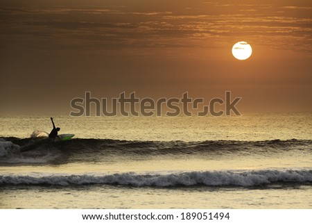 Surfer making a perfect turn in a beautiful sunset in northern Peru, South America.