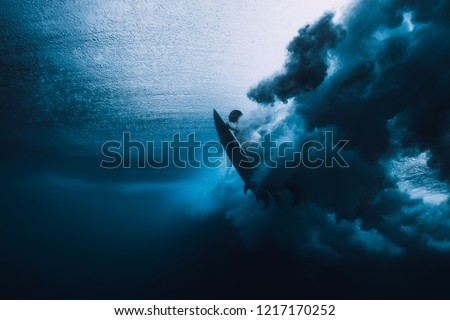 Surfer man with surfboard dive underwater with under ocean wave.