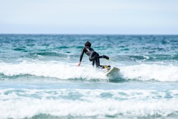 Surfer man with surfboard is falling in water. Guy in surfing wet suit is falling into the waves of cold Atlantic ocean in Galicia, Spain. Surfing accident concept.
