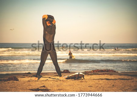Surfer on a beach. Man on a beach going to surf, carrying surfboard.