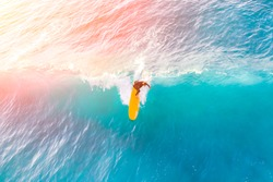 Surfer on a yellow surfboard in the ocean on a sunny day