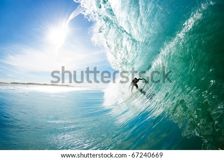 Surfer on Big Blue Ocean Wave Getting Barreled. Epic Surfing - stock photo