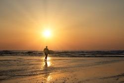 Surfer on the beach with sunburst at sunset porthtowan cornwall England uk