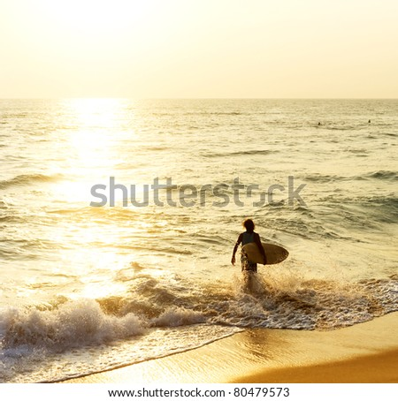 Surfer on the ocean beach at sunset in Hikkaduwa, Sri Lanka - stock photo
