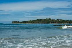 Surfer on the sea, turquoise water, blue sky. Arugam Bay, Sri Lanka. Portrait format