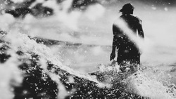 Surfer on the wave, catches a wave, surfing in the pipe. Surfing in the ocean on the island of Bali, a mellow man, a jump into the ocean. Taken from the water.