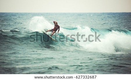Surfer on the wave. The surfer leaves the pipe. Waves on the island of Bali. Taken from the water. The surfer catches the wave