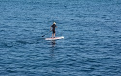 surfer paddling on his board