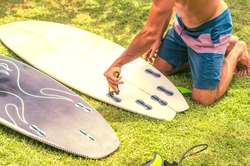 Surfer putting fins on a surfboard. Preparing a surf board for surf session.