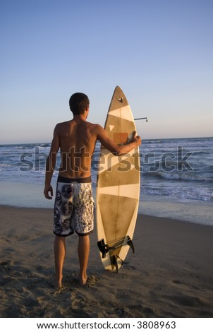 Surfer reasy to enter in the water at sunset