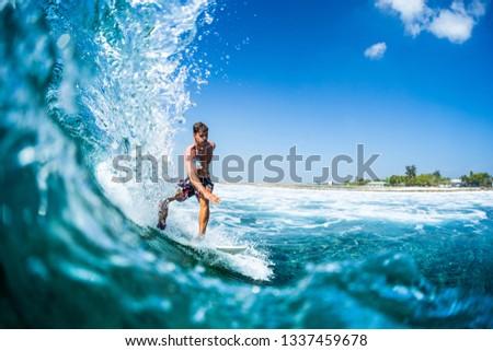 Surfer rides barreling tropical ocean wave #1337459678