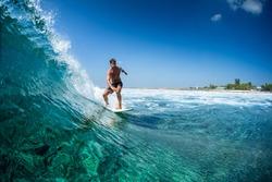 Surfer rides ocean wave in tropics