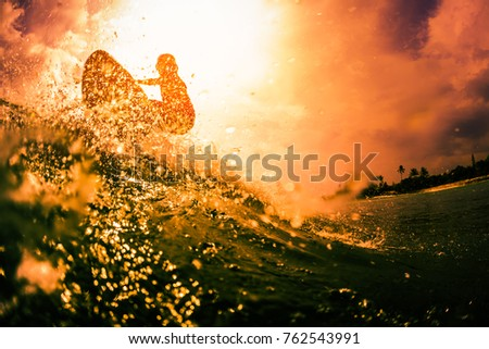 Surfer rides the ocean wave with lots of splashes. Extreme sport and action concept