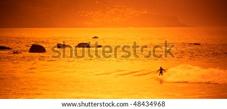 Surfer riding a wave in summer sunset.