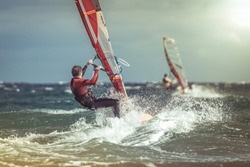 Surfer riding waves in a beautiful sunny day. Young man enjoying the wind and the ocean surfing in Tenerife island. Sea wave and surfers on the sea. Windsurfing, fun among the waves, extreme sport.