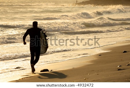 Surfer running on the beach at sunset