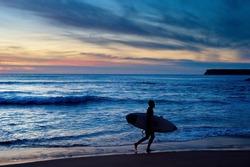 Surfer running with surfboard at dusk. Algarve, Portugal
