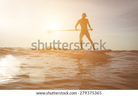 surfer silhouette at sunset.image with lens flare included for an artistic touch. concept about sport, surf, vacations and people