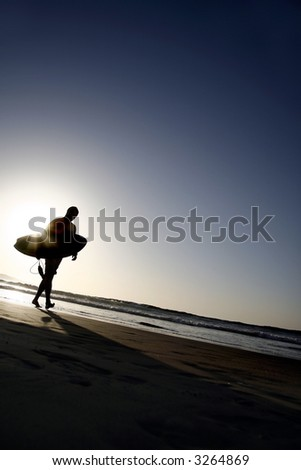 Surfer Silhouetted on an Empty Beach