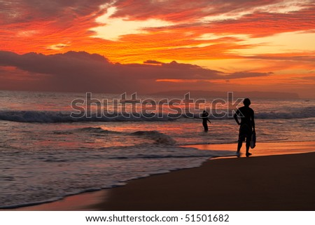 Surfer silhouetted on tropical ocean beach at sunset
