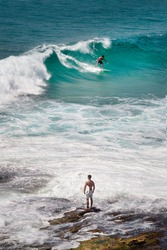 surfer stand on the rocks watching a buddy  surfing a wave on the coast between Bondi and Bronte, Sydney, Australia.