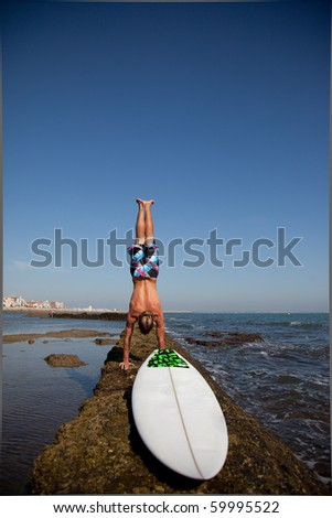 Surfer standing on his hands on a rock in the water with his board next to him