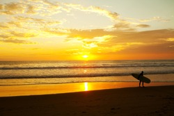 Surfer standing on the beach during a beautiful sunrise