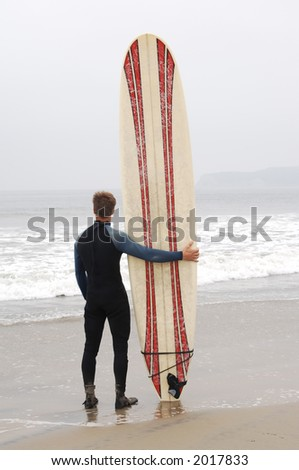 surfer standing on the beach with surfboard looking out to sea