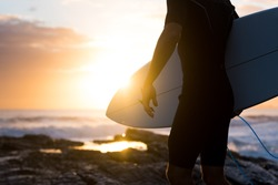 Surfer standing on the rocks at sunrise or sunset