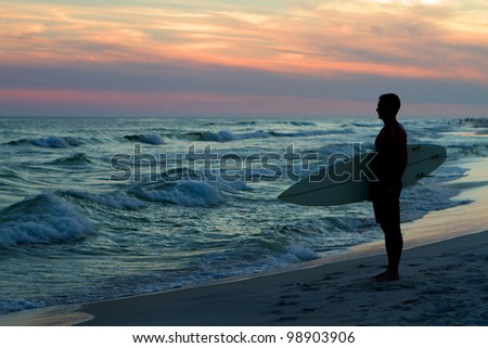 Surfer stands at the coastline holding his surfboard and watching the waves at sunset.