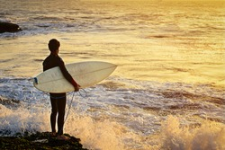 Surfer stands with a board on the Atlantic Ocean coast at sunset and waits for a suitable wave to start riding on a board and enjoy