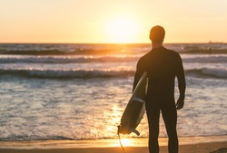 Surfer staring at the ocean and focusing on his goals. Sport and people concept