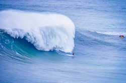 Surfer surfing massive waves at Nazare Portugal