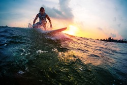 Surfer trying to catch the ocean wave during sunset. Active lifestyle and extreme sport concept