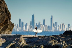 Surfer walking along a rocky coastline with the Gold Coast city skyline in the background.