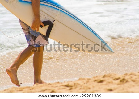 Surfer walking on sandy beach in Bali, Indonesia.