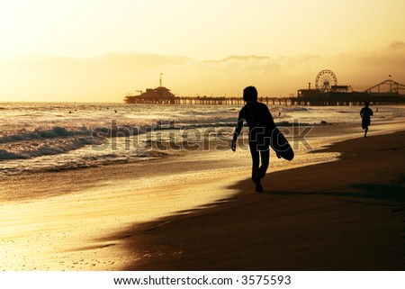 Surfer walking on the beach at sunset -Santa Monica pier in the background