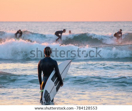 Surfer watching his friends surfing from the shore  Сток-фото ©