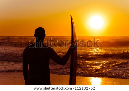 Surfer watching the waves at sunset in Portugal.