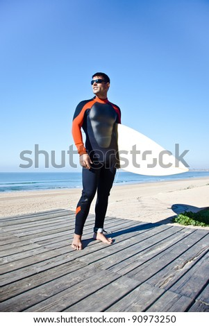 Surfer wearing a long wetsuit holding his surf board.