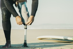 Surfer wearing wetsuit, standing by surfboard on sand and adjusting artificial limb taped to leg. Cropped shot. Artificial limb and active lifestyle concept