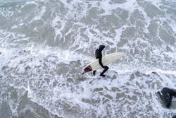 Surfer wearing wetsuit with surfboard watching ocean waves crash over rocks at St. Clair beach, Dunedin, New Zealand.