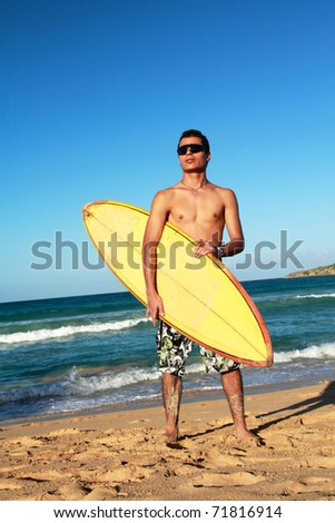 Surfer with a surfboard on tropical beach